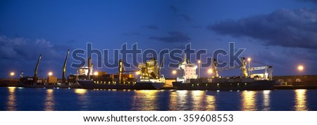 Panorama with ships and cranes near night pier with illumination  - stock photo