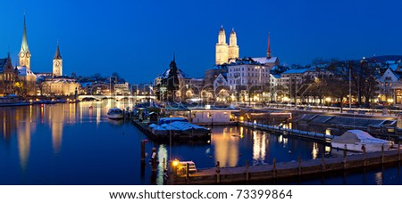Panorama: Zurich, swiss financial center seen from river Limmat at night with historic city center and it's churches reflecting in the stream - stock photo