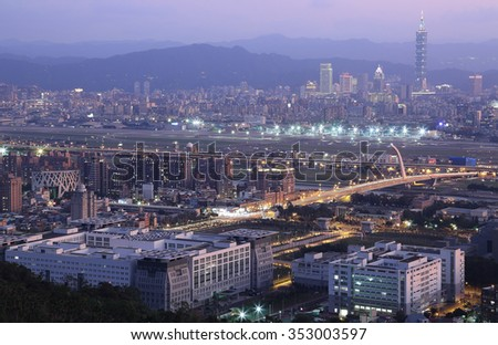 Panoramic aerial view of busy Taipei city, Keelung River, Dazhi Bridge, Songshan Airport and downtown area at dusk ~ A romantic evening in Taipei, Taiwan, with beautiful rosy afterglow in the sky - stock photo