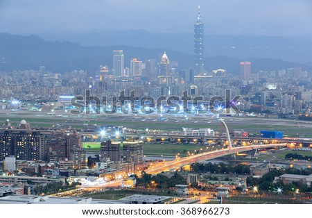 Panoramic aerial view of busy Taipei city, Keelung river, Dazhi Bridge, Songshan Airport and Taipei 101 at dusk ~ A romantic evening in Taipei Taiwan, with beautiful blue gloomy mood in the sky - stock photo