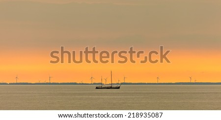 Panoramic image of a sailing boat at the Dutch Markermeer during sunset with wind turbines in the background - stock photo