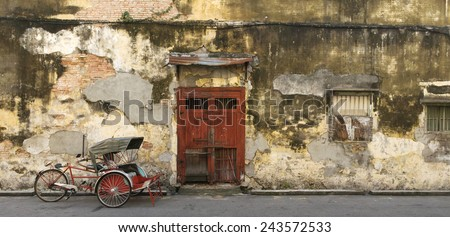 panoramic image of an old red door and trishaw in George Town, Penang, Malaysia - stock photo