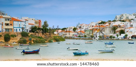 Panoramic image of Ferragudo harbour, showing the old town to the right, and new developments to the left - stock photo