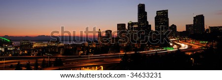 Panoramic image of Seattle downtown buildings and adjoining freeways with sunset glow over the horizon - stock photo