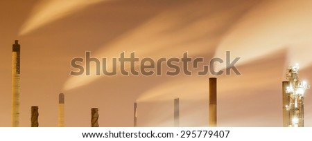 Panoramic image of smoke and chimneys of a large oil-refinery plant at night - stock photo