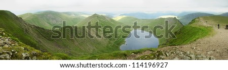 Panoramic landscape from the summit of Helvellyn, England's 2nd highest mountain, including Red Tarn and Striding Edge - stock photo