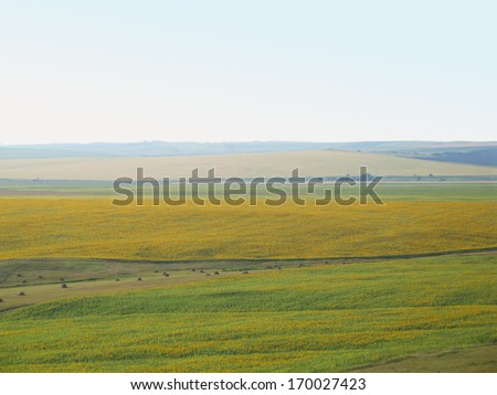 Panoramic landscape with a green field in the foreground. - stock photo