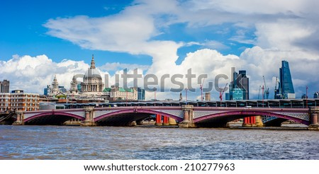 Panoramic London skyline including Blackfriars Bridge, St Paul's Cathedral and the skyscrapers of the City under a dramatic sky. - stock photo