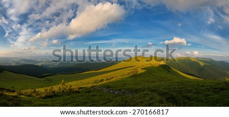 Panoramic mountains landscape with yellow flower meadow hills and slopes and cloudy sky - stock photo
