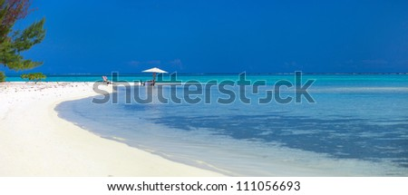 Panoramic photo of a table set on deserted tropical beach for an exotic picnic - stock photo
