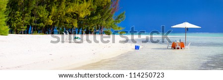 Panoramic photo of a tropical beach with picnic table set in a shallow water - stock photo