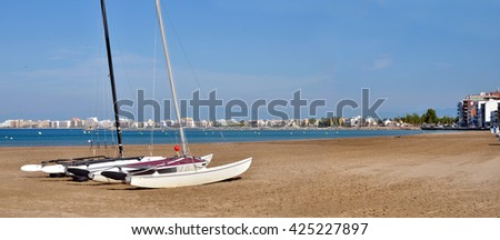 Panoramic photo of catamarans on the beach of Roses, or Rosas, commune on the Costa Brava at northeastern Catalonia in Spain - stock photo