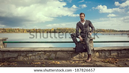 Panoramic photo of handsome man on the lake - stock photo