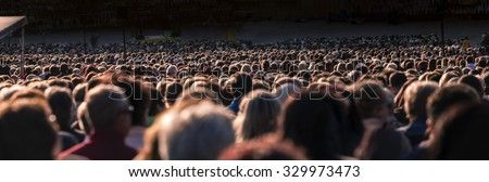 Panoramic photo of large crowd of people. Slow shutter speed motion blur. - stock photo