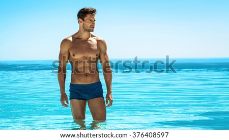Panoramic photo of sexy man posing in swimming pool - stock photo