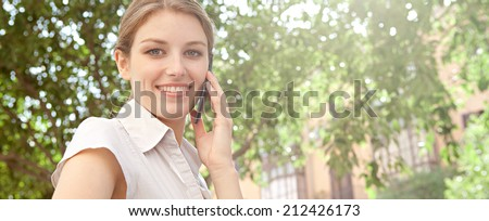 Panoramic portrait of a beautiful professional young business woman using her smartphone device to have a phone call conversation, working in the financial city, outdoors. Business people at work. - stock photo