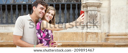 Panoramic portrait of an attractive young couple relaxing taking a selfie picture of themselves with a smartphone while visiting a destination city on holiday, together outdoors. Technology lifestyle. - stock photo