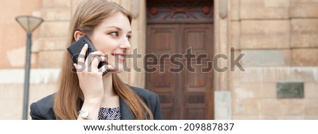Panoramic portrait of an elegant professional business woman standing by a grand stone building in the city, smiling and making a phone call with her smartphone device. Business technology outdoors. - stock photo