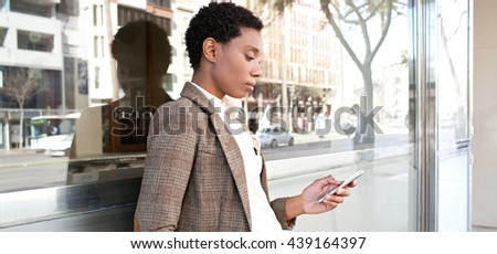 Panoramic portrait of beautiful african american business woman with reflective office building in financial city using smart phone, outdoors. Professional black woman technology lifestyle, exterior. - stock photo