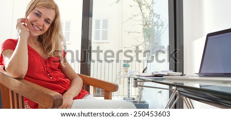 Panoramic portrait of young woman in her home office desk space using a laptop computer to work on, home interior. Student girl smiling using technology at home. Lifestyle and technology indoors. - stock photo
