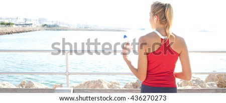 Panoramic rear view of healthy teenager girl contemplating the sea, sport exercise, holding mineral water bottle and listening to music with headphones, sunny day, coastal exterior. Sporty lifestyle. - stock photo