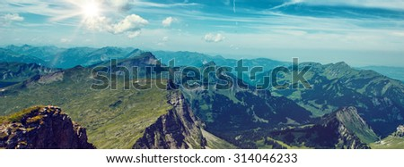 Panoramic Scenic View of Expansive Green Mountain Range with Bright Sun and Blue Sky - stock photo