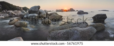Panoramic shot of a sunset over a rocky beach - stock photo