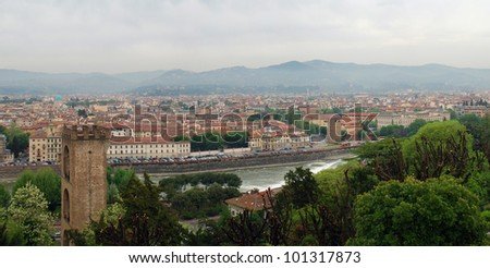 Panoramic shot of Florence seen from Michelangelo square: Old Tower, Arno River and hills in the horizon. - stock photo