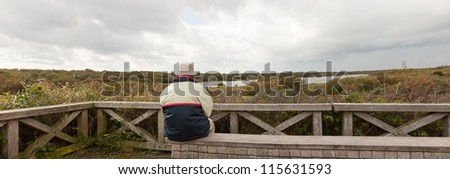 Panoramic shot of senior retired man sitting on bench enjoying the outdoors. Dutch dune landscape with stormy cloudy sky. Lonely man. The Netherlands. Wadden island. Texel. - stock photo