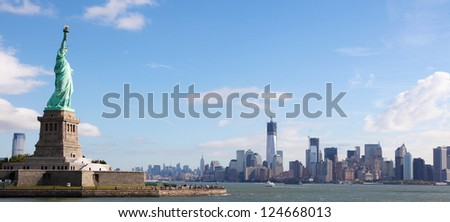 Panoramic skyline of Manhattan with the Statue of Liberty in New York City, US - stock photo