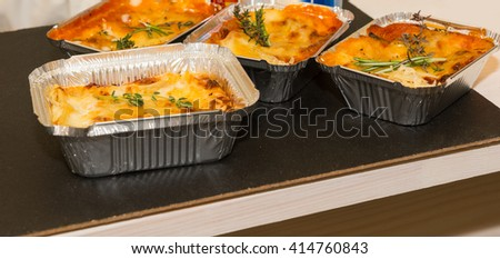 Panoramic Still Life of Foil Trays Filled with Cheesy Baked Entrees Garnished with Fresh Herbs and Cooling on Table with Copy Space - stock photo