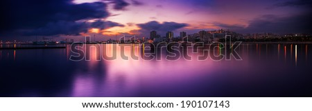 Panoramic sunset of cityscape with reflection in the sea - stock photo