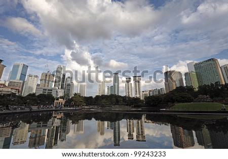 Panoramic urban city skyline of Kuala Lumpur city centre with reflection of skyscrapers and dramatic clouds in a lake. - stock photo