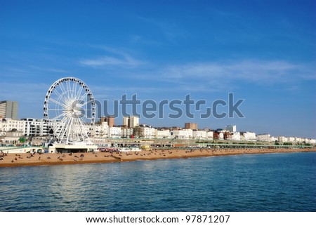 Panoramic view along Brighton Beachfront with the promenade and Ferris Wheel backed by highrise buildings - stock photo