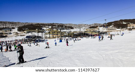panoramic view at ski resort village from snowy hill on sunny winter day cold and snow sport people having fun skiing and snowboarding - stock photo