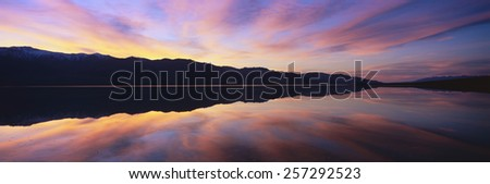 Panoramic view at sunset of flooded salt flats and Panamint Range Mountains in Death Valley National Park, California - stock photo