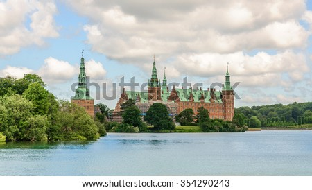 Panoramic view from the other side of the lake around Castle Frederiksborg Slot, Hillerod, near Copenhagen, Denmark - stock photo