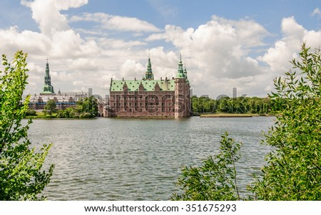 Panoramic view from the other side of the lake around Castle Frederiksborg Slot (with green grass and trees in foreground), Hillerod, near Copenhagen, Denmark - stock photo