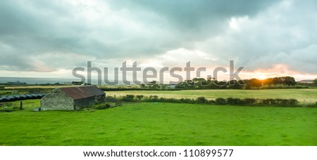 Panoramic view of a barn in a green field and orange sunrise in Northern Ireland - stock photo