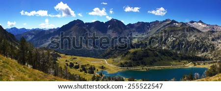 Panoramic view of a beautiful lake on the pyrenee mountains from the top of a summit with a view above the lush green valley with a mountain range in the background. - stock photo