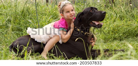 Panoramic view of a pretty young girl wearing a pink fancy dress, sitting on her dogs back enjoying a sunny holiday in a green park field, hugging him outdoors. Active family with pets, lifestyle. - stock photo