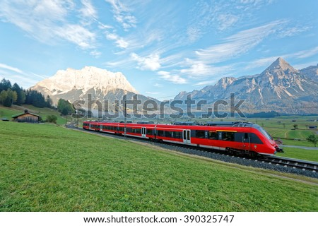 Panoramic view of a train traveling on green fields with Mountain Zugspitze in background on a beautiful sunny day in Lermoos, Tirol Austria ~ Beautiful autumn scenery of idyllic Tyrolean countryside - stock photo