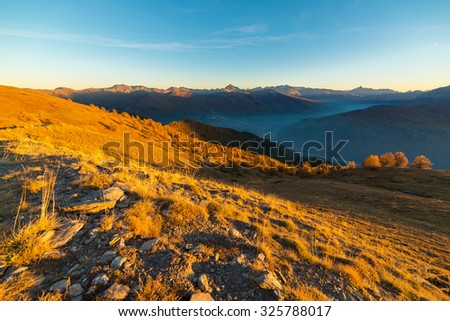 Panoramic view of alpine misty valley and mountain range in a colorful autumn with yellow meadows and high mountain peaks in the background. Wide angle shot at sunset. - stock photo