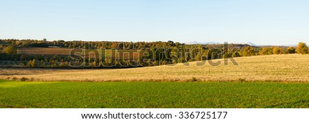 Panoramic view of autumn landscape with cultivated lands in the foreground and groves, oak and pine forests and mountains in the background on the plane last  - stock photo