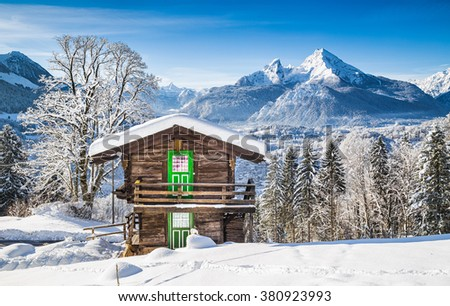 Panoramic view of beautiful white winter wonderland mountain scenery in the Alps with traditional mountain chalets on a cold sunny day with blue sky and clouds - stock photo