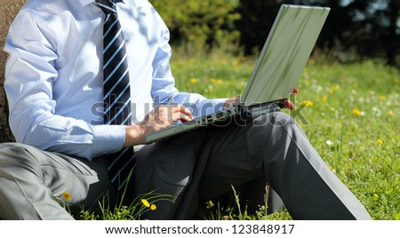 panoramic view of businessman working with laptop outdoor - stock photo