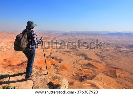 Panoramic view of color stone desert of Negev and traveler on the mountain top. National geological park HaMakhtesh HaGadol - Large Crater - a geological erosion land form, Israel - stock photo