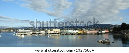 Panoramic view of colorful pier at Monterey, California, reflected in blue water - stock photo