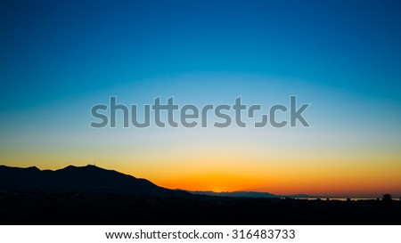 Panoramic view of dark Silhouette of Mountains on colorful sunrise sky background - stock photo