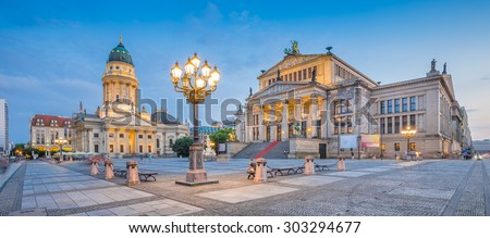 Panoramic view of famous Gendarmenmarkt square with illuminated Berlin Concert Hall and German Cathedral in twilight during blue hour at dusk, Berlin Mitte district, Germany - stock photo